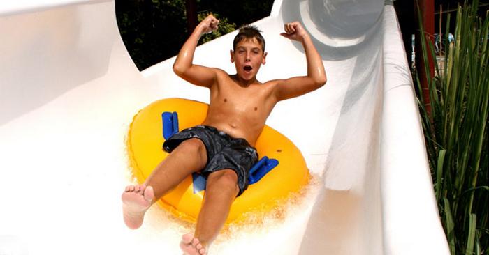 Boy riding tube down waterslide