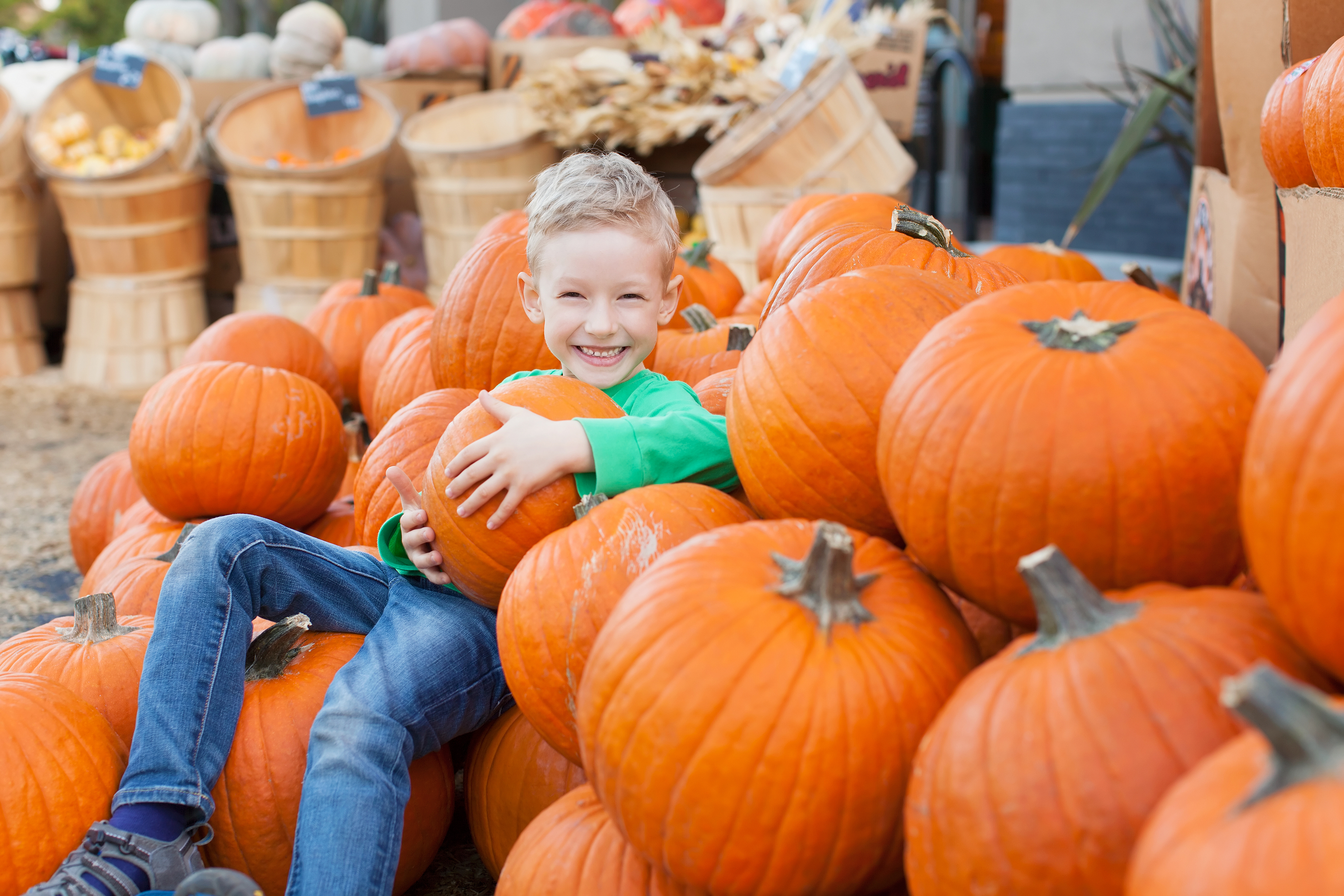 boy sitting among pumpkins in fall